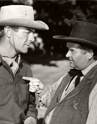 Randolph Scott as Brazos Kane listens to Charles Kemper as Sheriff Kiscaden in Gunfighters (1947)
