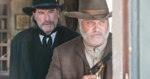 John Travolta as the marshal with Tommy Nohilly as Tubby in In the Valley of Violence (2016)