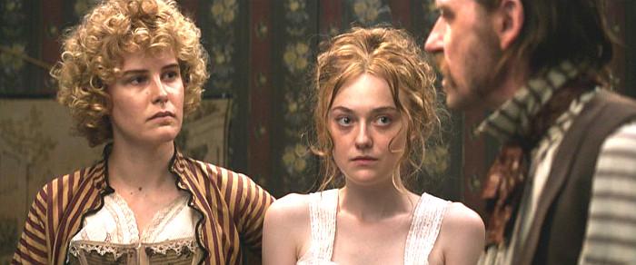 Carla Juri as Elizabeth and Dakota Fanning as Joanna listening to Paul Anderson as Frank in Brimstone (2016)