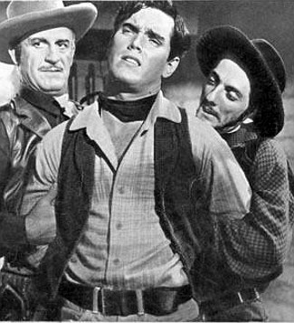 Jeffrey Hunter as Johnny Colt in the hand of two of Apache Joe's men, including (right) Aaron Spelling as Catur in Three Young Texans (1954)