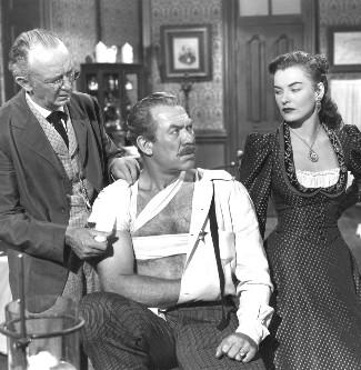 Walter Brennan as Dr. Jonathan Mark, Ward Bond as Sheriff Jim Caradoc and Ella Raines as Nan Moran in Singing Guns (1950)