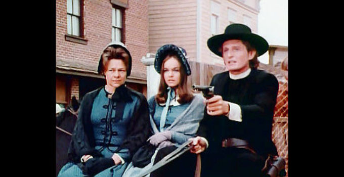 Marjoe Gortner as Ernie Parsons keeps two of Mr. Ross's men at bay while in the company of Sadie (Estelle Parsons) and Sally Underwood (Pamela Sue Martin) in The Gun and the Pulpit (1974)